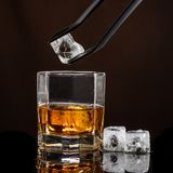 Heksagonalny szk?o whisky z lodem na ciemnym tle i liczb? istni kostka lodu zdjęcie royalty free
