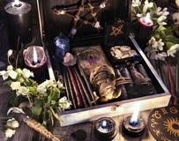 Heksenvakje met zwarte kaarsen, tarotkaarten, runen, voodoopop en magische voorwerpen met bloemen stock foto's