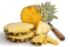 Hel ananas klippte upp med stycken och baktalar Arkivfoton