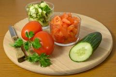 Hel gurkor, tomater och sallad av dem på en skärbräda Royaltyfri Bild