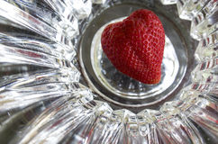 Hel jordgubbe som är okrönt i formen av hjärta på abstrakt bakgrund Royaltyfri Bild