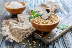 Hel kornhavre och skopa av mjöl i en träbunke Arkivfoton