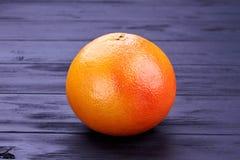 Hel ny grapefrukt på mörkt trä royaltyfria foton