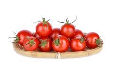 Hel ny röd körsbärsröd tomat i korgen och på den vita backgroen Fotografering för Bildbyråer
