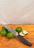 Hel och skivad limefrukter och kniv Royaltyfri Fotografi