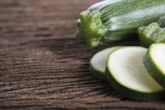 Hel och skivad ny zucchini på träbakgrund Royaltyfri Foto