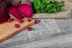 Hel och skivad rödbetor, persilja och dryck på en skärbräda och på en träbakgrund Grönsaker från trädgård royaltyfri fotografi