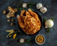 Hel rå höna i järnpanna marinerade och ordnar till för att laga mat med ingredienser för att laga mat På stenbakgrund Royaltyfria Bilder