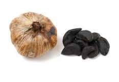 Hel svart vitlök och kryddnejlikor Arkivbild