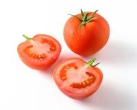Hel tomat och halv en tomat som isoleras på vit Royaltyfri Fotografi