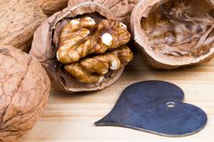 Hel valnötter och valnötkärna på den lantliga trätabellen med en hjärta Arkivbilder