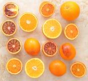 Hela apelsiner och snitt i halva på en marmorbakgrund Bakgrund Fotografering för Bildbyråer
