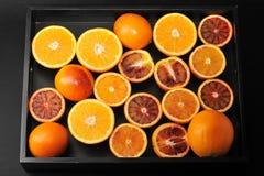 Hela apelsiner och snitt i halva på ett svart magasin bakgrund från c Royaltyfri Fotografi