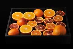 Hela apelsiner och snitt i halva på ett svart magasin bakgrund från u Royaltyfria Foton