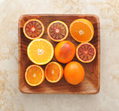 Hela apelsiner och snitt i halva på ett wood magasin bakgrund från oss Arkivbild