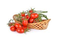 Hela nya mogna tomater med stammen i korgen och på vit b Arkivfoton