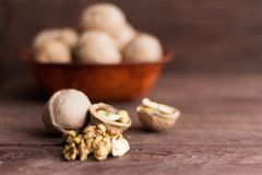 Hela och kluvna valnötter på träbakgrund arkivfoton
