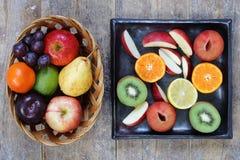 Hela och skivade frukter på den lantliga wood tabellen Arkivbilder