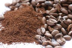 Hela och slipade spridda kaffebönor Arkivfoto