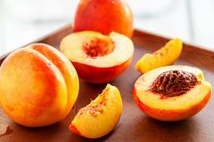 Hela organiska frukter för mogna saftiga nektariner och skiva på träbakgrund Arkivbild
