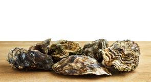 Hela ostron på en träyttersida arkivbilder