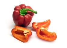 Hela två och cutted röda mogna spanska peppar som isoleras på det vita bakgrundsslutet upp Royaltyfria Foton