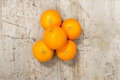 Hela Unpeeled apelsiner på en träyttersida Royaltyfria Bilder