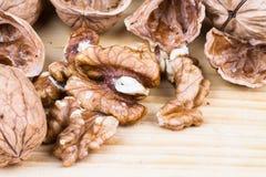 Hela valnötter och valnötkärnor på den lantliga trätabellen Arkivbild