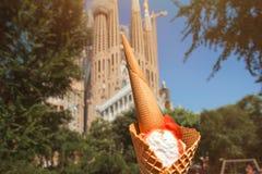 Helado anaranjado y blanco en el fondo de la falta de definición Sagrada Familia en Barcelona imagenes de archivo