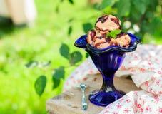Helado de chocolate con la salsa de dulce de azúcar en un cuenco azul Fotos de archivo libres de regalías