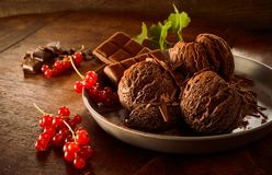 Helado de chocolate con las pasas rojas en plato Fotos de archivo