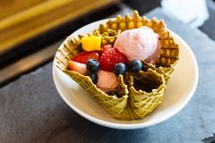 Helado de fresa con las frutas frescas dentro del cuenco fino curruscante de la galleta foto de archivo libre de regalías