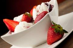 Helado de la fresa en un cuenco blanco con las fresas Imágenes de archivo libres de regalías
