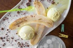 Helado de la fruta con el plátano fresco asperjado con el chocolate en la placa blanca Imagen de archivo libre de regalías