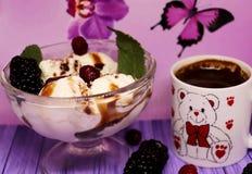 Helado delicioso de vainilla, con el chocolate y la fruta, con una taza de café natural en un fondo de mariposas púrpuras fotografía de archivo