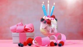 Helado rosado del helado con las velas del cumpleaños Fotos de archivo libres de regalías