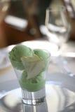 Helado verde que derrite en un vidrio Imagenes de archivo