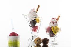Helados coloridos del helado, y taza para llevar en el fondo blanco Imagenes de archivo