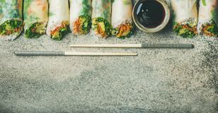 Vegan spring rice paper rolls over concrete background, copy space. Helathy Asian cuisine. Flat-lay of vegan spring rice paper rolls with vegetables, soy sauce Royalty Free Stock Photography