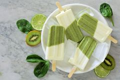 Helathy green smoothie popsicles on a marble plate. Healthy green smoothie popsicles with kiwi, lime and spinach on a white marble plate, overhead view Royalty Free Stock Photography