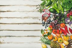 Helathy raw vegan food cooking background over white table. Helathy raw vegan food cooking background. Flat-lay of fresh fruit, vegetables, greens, superfoods royalty free stock images