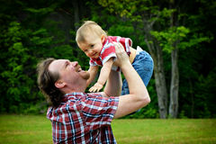 Held Aloft. Father holding baby in the air both smiling, in an outdoor setting stock images