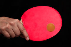 Held backhand in shake hand styleto hit orange table tennis ball Stock Images