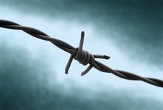 Held in Fear!. Barbed wire with dramatic and very cold backround. Looks as best at full size with dark background royalty free stock photography