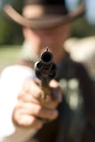 Held at Gunpoint. Cowboy aiming gun, focus only on gunpoint Royalty Free Stock Photo