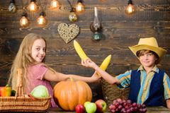 Held responsible for daily farm chores. Kids farmers girl boy vegetables harvest. Children presenting farm harvest. Wooden background. Family farm. Reasons why royalty free stock photos