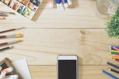Held-Titel-Konzept ein Schreibtisch des Künstlers und des Smartphone lizenzfreie stockbilder