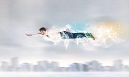 Heldensuperman die boven stad met erachter verlaten rook vliegen Stock Fotografie