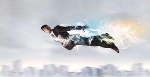 Heldensuperman die boven stad met erachter verlaten rook vliegen Royalty-vrije Stock Fotografie