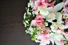 Helder bloemenboeket van lelies en een donkere houten lijst Stock Afbeelding